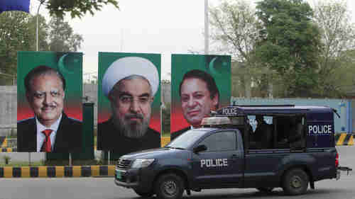 Posters with portraits of Iran's president Hassan Rouhani in the center, with Pakistan's prime minister Nawaz Sharif on the right, and Pakistan's president Mamnoon Hussain on the left, Islamabad on Friday (Reuters)