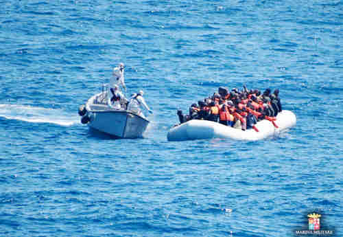 Italian Navy personnel, left, approach a rubber dinghy filled with migrants in the Sicily channel, Mediterranean Sea (AP)