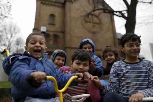 Migrant children from Syria pose in front of a Protestant church in Oberhausen, Germany, November 19, 2015 (Reuters)