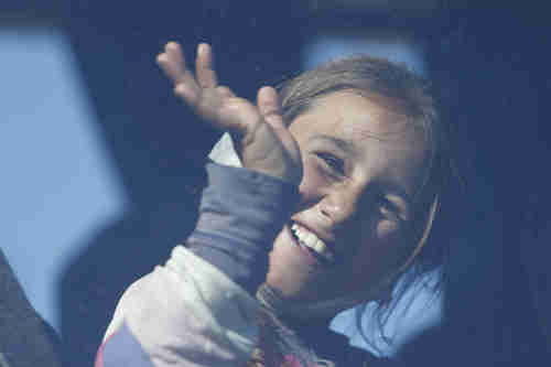 An Iraqi Yazidi girl waves from a bus as she and her family leave the Idomeni refugee camp and head for another camp in Greece on Tuesday (AP)