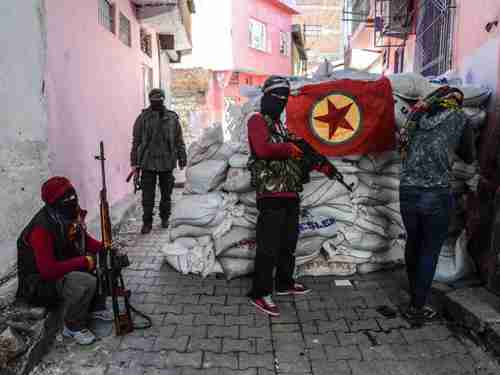 The PKK flag hangs as armed PKK militants man a barricade in southeastern Turkey on November 15 2015 (AFP)