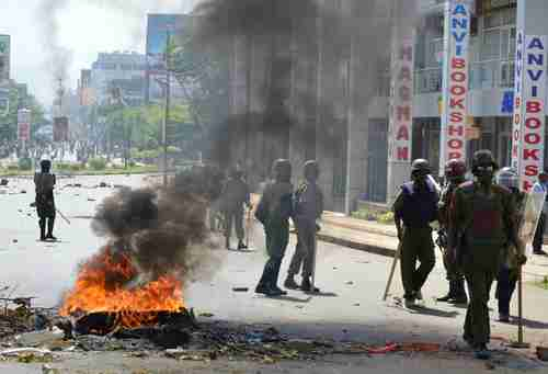 Police officers walk past burning tyres in Kisumu, Kenya, on Monday (AFP)