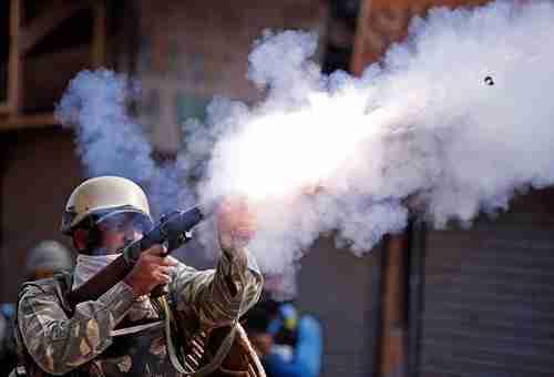 An Indian policeman fires a teargas shell at Srinagar, Kashmir, protestors on Tuesday (Reuters)