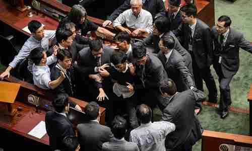 Newly elected lawmaker Baggio Leung is restrained by security while attempting to deliver his oath of office (AFP)