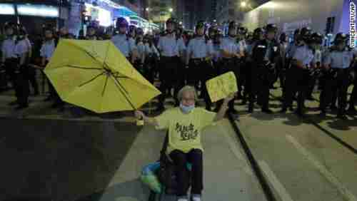 A protester raises a yellow umbrella in front of a line of police officers in Hong Kong on Sunday