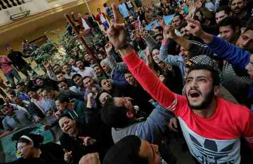 Egyptian Christians shout slogans in front of riot police outside a Cairo church on Monday (Reuters)