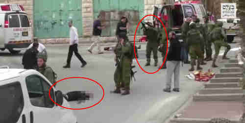 Screen grab from video of March 4, 2016. Israeli soldier reloads his gun just before shooting dead the Palestinian lying wounded and bleeding (AP)
