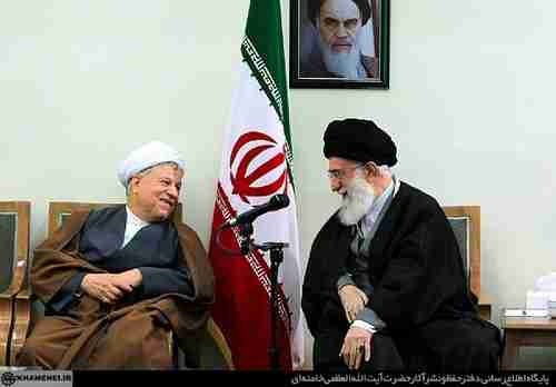 Hashemi Rafsanjani (L) shares a laugh with Supreme Leader Ali Khamenei, under a photo of the original Supreme Leader, Rouhollah Khomeini.  All three fought together in the 1979 revolution.