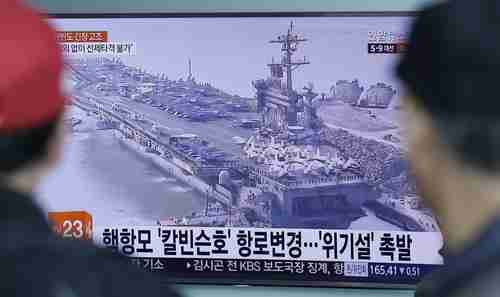 People in Seoul, South Korea, watch a TV news program showing a file image of the USS Carl Vinson aircraft carrier on Wednesday.  The caption reads 'The USS Carl Vinson aircraft carrier changes route.' (AP)