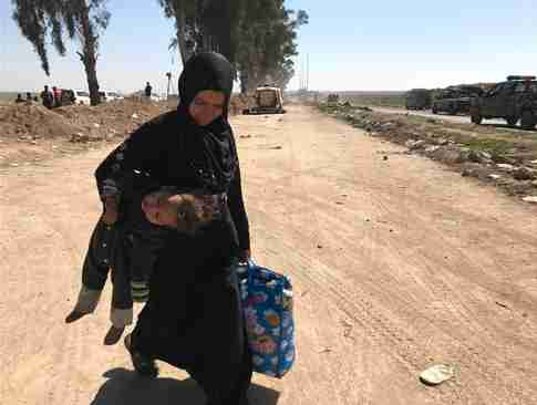 Woman fleeing Mosul carries her child in one hand and a bag of belongings in the other (CNN)