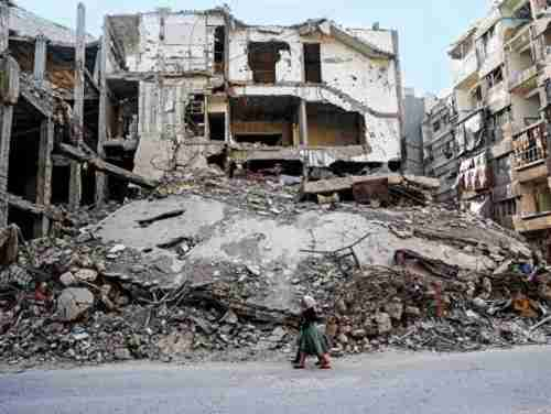 Two girls walk past destroyed buildings in Douma, Syria, part of a planned 'safe zone' (AFP)
