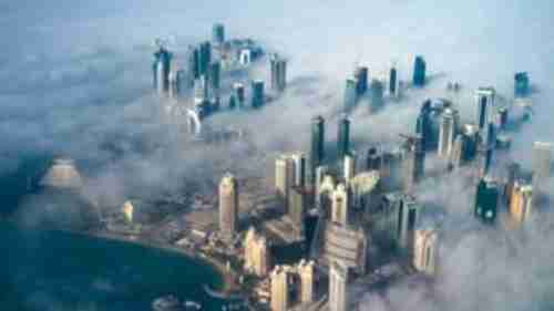 An aerial view of Doha, Qatar, in the fog, as the sun rises