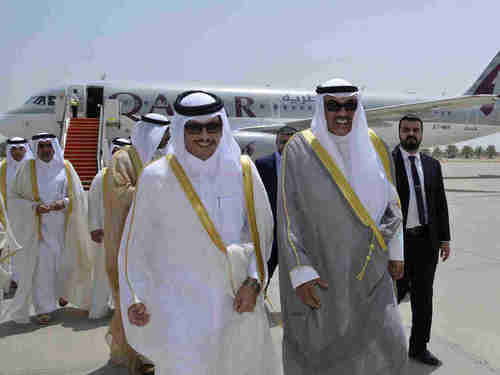 Qatar's Foreign Minister Sheikh Mohammed bin Abdulrahman Al Thani (L) and Kuwaiti Foreign Minister Sheikh Sabah Khaled Al Sabah walk together on an airport tarmac in Kuwait. (AP)