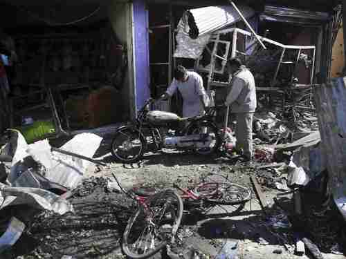Men look at the remains of their properties at the site of the car bombing Monday in Kabul (AP)