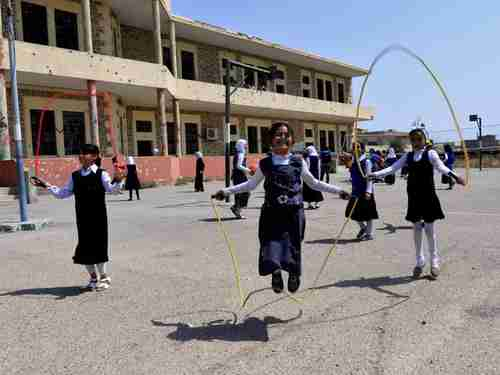 Iraqi girls play in a Mosul schoolyard (Reuters)