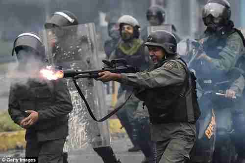 A member of the national guard fires his shotgun during clashes in Caracas, Venezuela, in July (Getty)