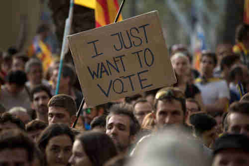 In Barcelona on Thursday, a protesters holds up a banner reading 'I just want to vote' (Getty)