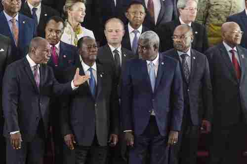 Guinea's President Alpha Conde, front row left, speaks with Ivory Coast President Alassane Ouattara, front row middle, and African Union Commission chairman Moussa Faki, front row center, during group photo on Wednesday at AU-EU Summit. (AP)