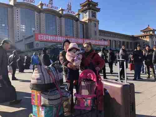 A migrant family is leaving Beijing under a government-mandated evacuation. They had 15 mins to clear all their belongings. Behind them is a big banner saying the great 'Xi Jinping new era'. (Twitter)