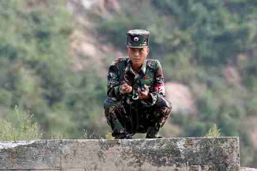 A North Korean soldier squats along the Yalu River in Sinuiju, North Korea, which borders Dandong in China's Liaoning province, Sept 9, 2017.