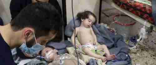 Medical workers treat toddlers following chlorine gas attack in Douma, Syria, on Sunday (AP)