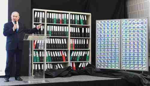 Israel's prime minister Benjamin Netanyahu stands next to a facsimile of the intelligence archive that Mossad had taken from a Tehran warehouse in January (Times of Israel)