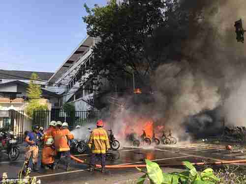 Firefighters try to extinguish a blaze following a blast at the Pentecost Church Central Surabaya in Indonesia on Sunday (Reuters)