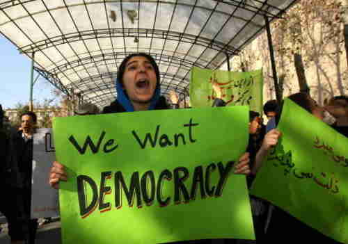 Protester in Tehran, Iran, on Monday with banner, 'We Want Democracy!' (Getty)