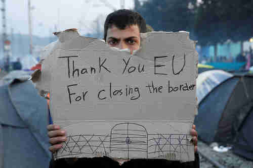 A migrant holds a sarcastic protest sign after failing to enter the EU (Reuters)