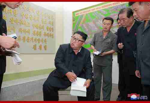 Kim Jong-un makes a big show of taking notes at a factory in this North Korean media photo
