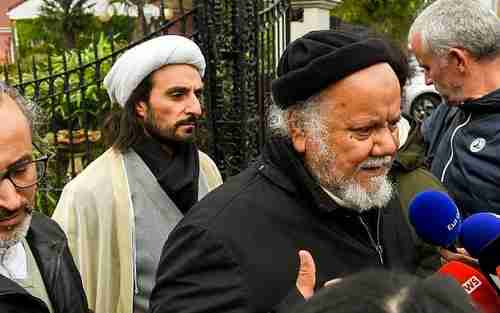 Gouasmi Yahia (R), founder of the Zahra Center France religious association, speaks to reporters after his offices were raided by police on Tuesday (AFP)