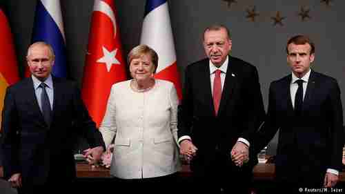 Leaders holding hands: Vladimir Putin, Angela Merkel, Recep Tayyip Erdogan, and Emmanuel Macron (Reuters)