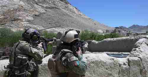 An Afghan command and a US Special Forces soldier scan the horizon for enemy movement in Afghanistan, on May 24, 2018. (Military Times)