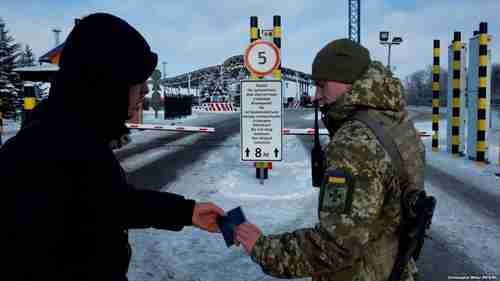 Ukrainian border guards prevent Russian men, aged 16-60, from entering Ukraine.  Sign says: 'Do not stop between the striped columns.' (RFE/RL)