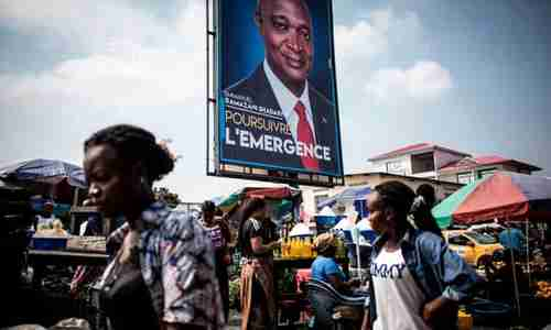 Women walk past a campaign poster of Joseph Kabila's chosen successor as president of DRC, Emmanuel Ramazani Shadary, in Kinshasa on Dec 18 (AFP)