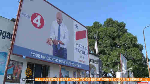 Leading opposition DRC candidate Martin Fayulu - campaign poster showing him buttoning or unbuttoning (I can't tell which) his shirt cuffs (Al-Jazeera)