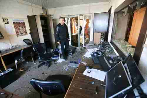 Employee inspects damage to Palestinian Authority media office in Gaza after attacks by five men (AFP)
