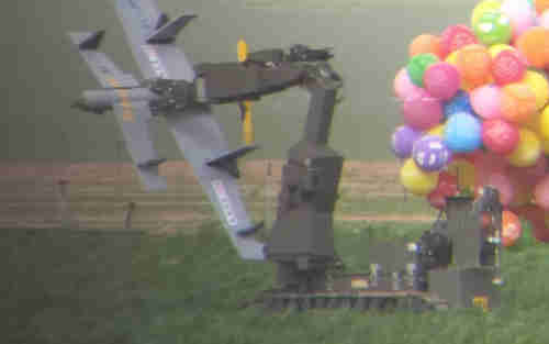 A police bomb disposal robot carries away a drone-shaped device from a carrot field that had been flown in from Gaza by a cluster of helium balloons on Sunday.  (Israel Police)