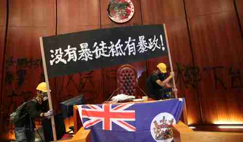 Protesters install an old British colonial flag in the Legislative Council chamber on Monday (SCMP)
