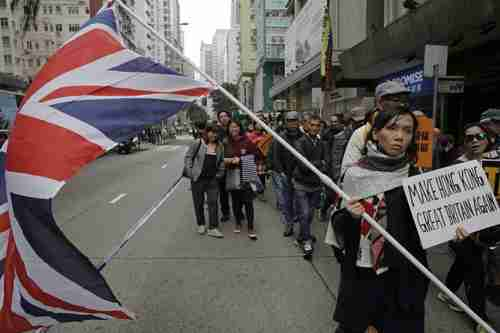 In a previous protest, girl holds British flag and placard reading 'Make Hong Kong Great Britain Again' (SCMP)