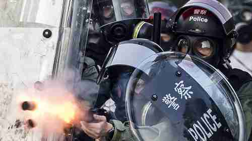 Riot police fire projectiles against protesters in Hong Kong on Tuesday (Sky News)