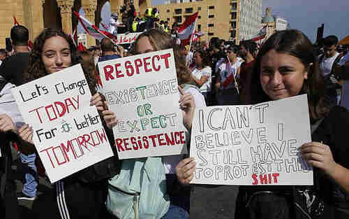 Girls holding anti-government placards during protests in Beirut, Lebanon, on Sunday (AP)