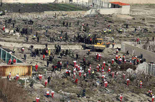 This image from Wednesday shows the crash site with a bulldozer burying the evidence so that Iran can deny culpability. (AP)