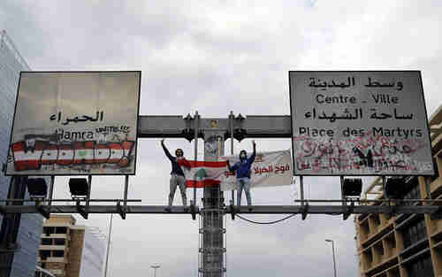 Anti-government protesters in Beirut, Lebanon, stand atop a road sign and flash the victory sign along a main highway that has been blocked by hundreds of protesters, on Friday. (AP)