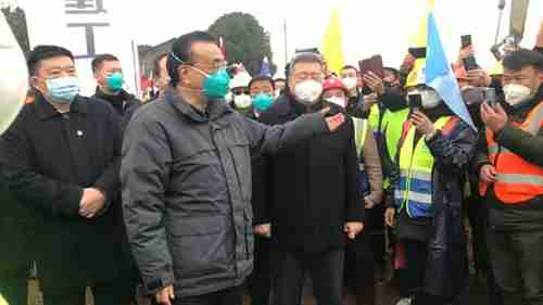 China's premier Li Keqiang, wearing a green medical mask, meets hospital workers in Wuhan on January 29 (AP)