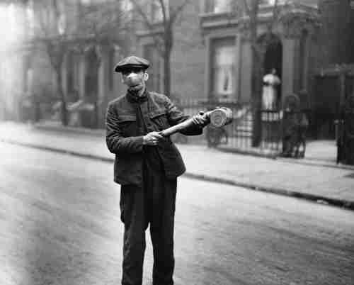 A man wearing a mask uses a pump to spray an unknown 'anti-flu' substance in the United Kingdom, following the Spanish flu pandemic (Getty)