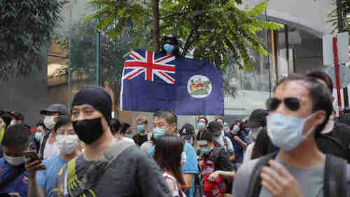 A protester displays the (British) Hong Kong colonial flag on Wednesday.  Under the new law, he could be sent to jail for 5 or more years.  (AP)
