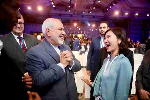 A hearty laugh is shared in December by Iran's foreign minister Javad Zarif, left, and Miao Lu, secretary-general of Center for China & Globalization (AFP)