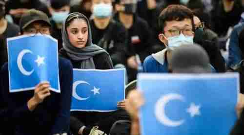 A rally in Hong Kong in December last year in support of Uighurs in Xinjiang province.  In the back, one officer draws a pistol.  (AFP)