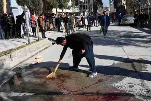 A Kabul resident washes the road after gunmen killed two female judges working for the Supreme Court (AFP)